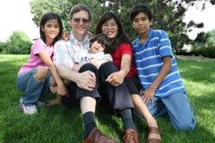 Familia multirracial grande que se sienta en césped Fotos de archivo libres de regalías