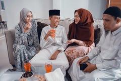 Familia musulmán feliz que tiene un vidrio de la bebida para el ayuno de la rotura fotografía de archivo