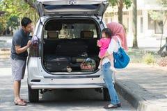 Familia musulmán joven, transporte, ocio, concepto del viaje por carretera y de la gente - hombre feliz, mujer y niña que juegan  imagen de archivo libre de regalías
