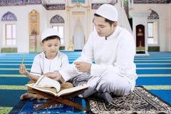 Familia musulmán que lee un Corán en la mezquita imagenes de archivo
