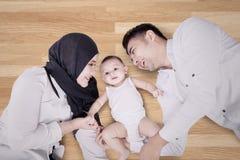 Familia musulmán que miente en el piso de madera Foto de archivo libre de regalías