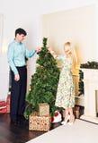 Familia, Navidad, vacaciones de invierno y concepto de la gente - par feliz adornando el árbol de navidad en casa Fotografía de archivo libre de regalías