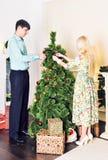 Familia, Navidad, vacaciones de invierno y concepto de la gente - par feliz adornando el árbol de navidad en casa Imagen de archivo