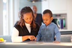Familia negra joven en cocina moderna fresca Fotos de archivo