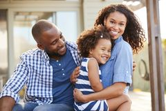 Familia negra que abraza al aire libre la sonrisa a la cámara afuera imagen de archivo