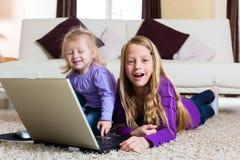 Familia - niño que juega con la computadora portátil Imagen de archivo
