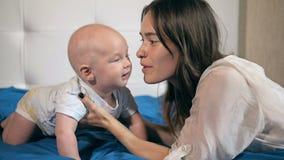 Familia, niño y concepto de la paternidad - madre feliz que besa al bebé sonriente metrajes