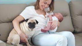 Familia, niños y animales felices Una madre joven está celebrando a un bebé recién nacido en sus brazos, sentándose en el sofá ne almacen de metraje de vídeo