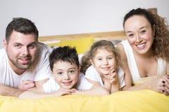 Familia, niños y concepto casero - familia feliz con dos niños debajo de la manta en casa Imagenes de archivo