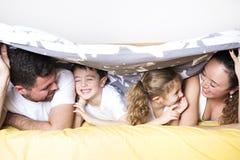 Familia, niños y concepto casero - familia feliz con dos niños debajo de la manta en casa Foto de archivo