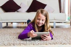 Familia - niño que juega con la pista del ordenador de la tablilla Foto de archivo libre de regalías