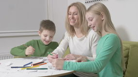 Familia o madre feliz con los niños lindos que dibujan con los lápices coloridos almacen de metraje de vídeo