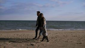 Familia, ocio y concepto de la gente - madre feliz, padre y peque?o hijo que caminan a lo largo de la playa del oto?o Vista later almacen de video