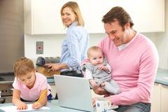 Familia ocupada junto en cocina Fotografía de archivo libre de regalías
