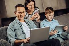 Familia optimista que trabaja en sus dispositivos Foto de archivo libre de regalías