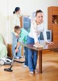 Familia ordinaria de limpieza de la casa que hace tres Foto de archivo