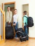 Familia ordinaria de tres con el equipaje que mira en espejo cerca de doo Imagen de archivo libre de regalías