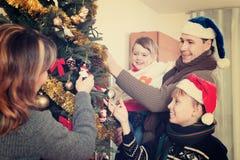 Familia ordinaria que adorna el árbol de navidad Foto de archivo