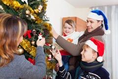 Familia ordinaria que adorna el árbol de navidad Fotos de archivo libres de regalías