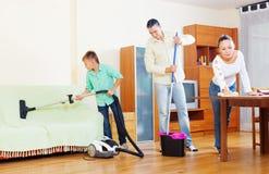 Familia ordinaria que hace la limpieza de la casa Foto de archivo libre de regalías