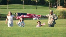Familia patriótica que corre con el fondo enorme de los E.E.U.U. al aire libre almacen de metraje de vídeo