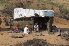 Familia pobre cerca de la choza de la paja en el desierto de Thar Rajasthán, la India Fotos de archivo