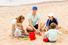 Familia positiva de cinco que se sientan en la playa arenosa Fotografía de archivo