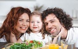 Familia positiva que cena sano con el disfrute imagen de archivo libre de regalías