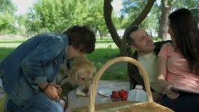 Familia positiva que disfruta de comida campestre con su perro almacen de metraje de vídeo