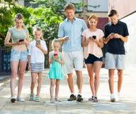 Familia positiva que juega con los teléfonos móviles Foto de archivo libre de regalías