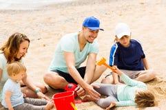 Familia positiva que juega en la playa arenosa Imagenes de archivo