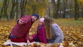 Familia positiva que toma el selfie en el teléfono móvil en otoño almacen de metraje de vídeo