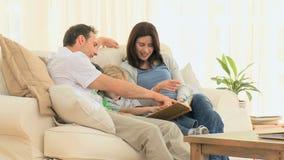 Familia preciosa que mira un álbum metrajes