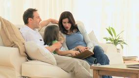 Familia preciosa que mira un álbum de foto almacen de metraje de vídeo