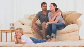 Familia preciosa que ve la TV almacen de metraje de vídeo