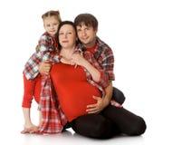 Familia que abraza a la mamá embarazada fotos de archivo
