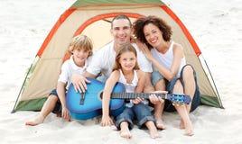 Familia que acampa en la playa que toca una guitarra Fotos de archivo libres de regalías