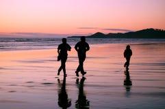 Familia que activa en la puesta del sol en la playa Foto de archivo