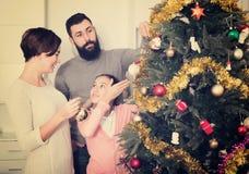 Familia que adorna el árbol Fotos de archivo libres de regalías
