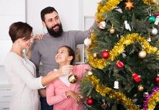 Familia que adorna el árbol Imagen de archivo