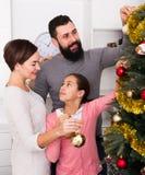 Familia que adorna el árbol Foto de archivo