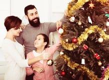 Familia que adorna el árbol Imágenes de archivo libres de regalías