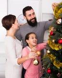 Familia que adorna el árbol Imagenes de archivo