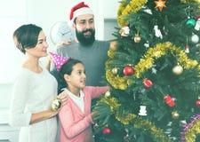 Familia que adorna el árbol Fotografía de archivo libre de regalías