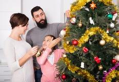 Familia que adorna el árbol Imagen de archivo libre de regalías