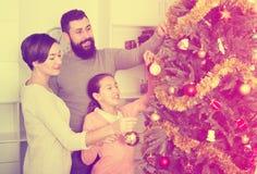 Familia que adorna el árbol Foto de archivo libre de regalías