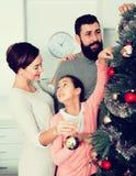 Familia que adorna el árbol Fotografía de archivo