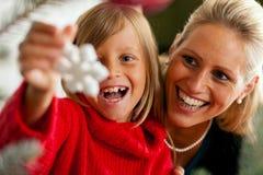 Familia que adorna el árbol de navidad Imagen de archivo libre de regalías