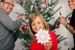 Familia que adorna el árbol de navidad Foto de archivo