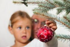 Familia que adorna el árbol de navidad Fotografía de archivo